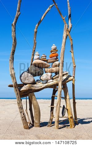 composition of the stones and dry tree on background of the sea. Rock zen on the beach