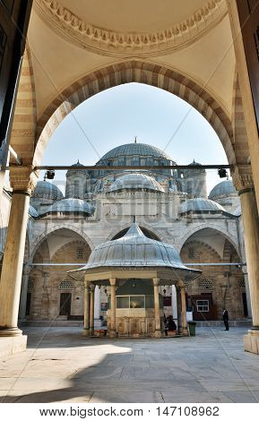 Istanbul, Turkey - November 5, 2015. View of Shehzade Mehmet mosque in Istanbul, from under an outer archade, with people.