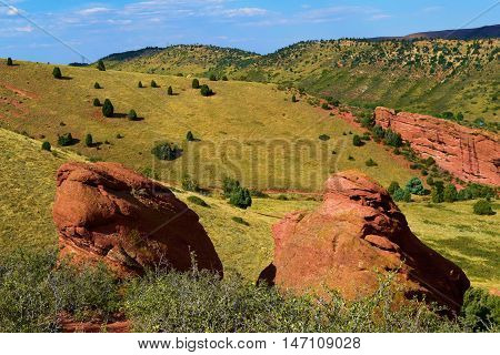 Red Rock Mesas covered in lush green grasslands taken at Red Rocks Park, CO