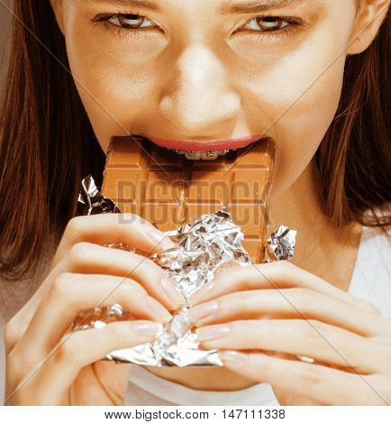 woman eating chocolate, close up hands with manicure french nails holding candy, beautiful fingers, diet concept