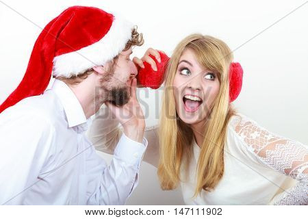 Man boyfriend in santa claus hat whispering to woman girlfriend ear. Gossip couple on gray. Christmas xmas season.
