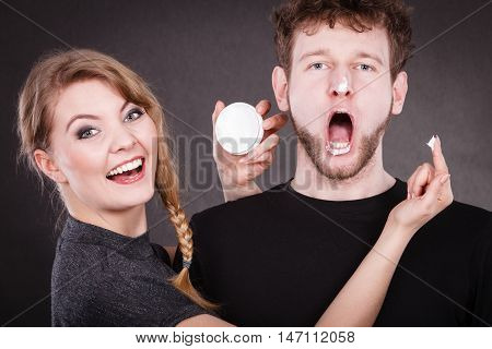 Woman Applying Cream To Her Man Face.