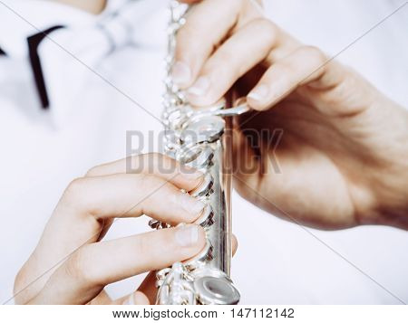 Hands of young man playing the flute. Male flutist musician performer holding instrument close up