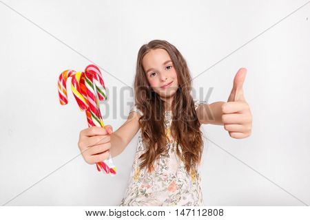 Happy, smiling cute little girl with cristmas candy canes. Saying Ok, Posing against a white wall.
