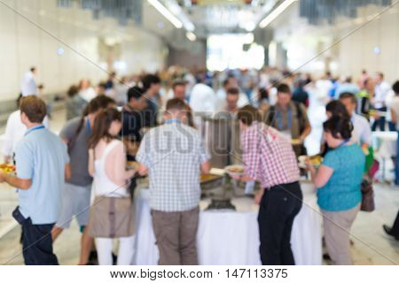 Abstract blurred people socializing during buffet lunch break at business meeting or conference.