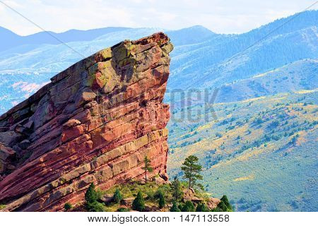 Large red rock with the Front Range of the Rocky Mountains beyond taken at Red Rocks Park near Denver, CO
