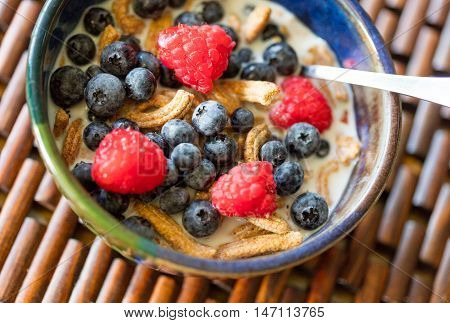 High fiber cereal with fresh blueberries and raspberries