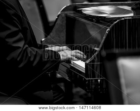 Close-up on a man's hand playing the piano, black & white
