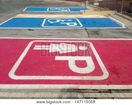 women parking symbol and handicapped parking symbol on floor