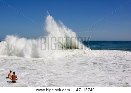 Two young men watch from the shallow wash of the ocean as giant wave breaks following a storm.