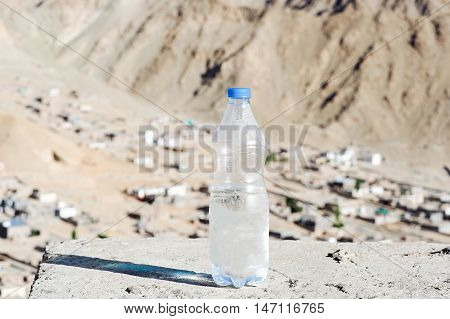 Bottle of water in desert land - hydration and dehydration concept.