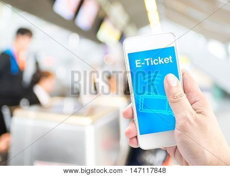 Hand Holding Mobile With E-ticket With Blur Airport Check-in Background, Digital Booking Concept