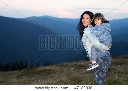 Happy mother and son piggyback in the moutains at sunset