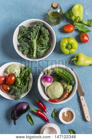 Fresh vegetables - broccoli peppers tomatoes eggplant squash turnips on a blue background top view. Cooking ingredients.