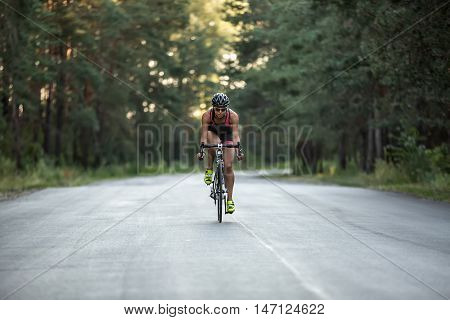 Horizontal photo of female cyclist in motion who rides a bike on the road on the nature background. She wears black-pink sportswear, a stopwatch, a black helmet, sunglasses and green sneakers.