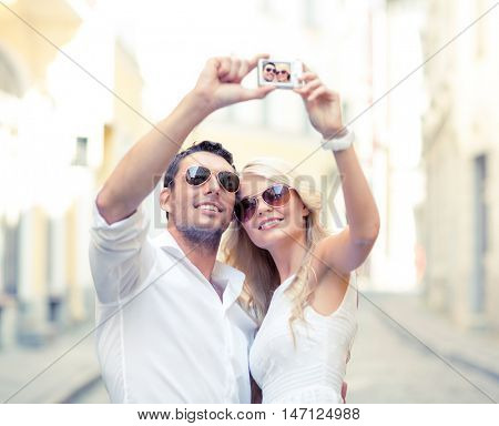 summer holidays, travel, vacation, tourism and dating concept - travelling couple taking photo picture with camera