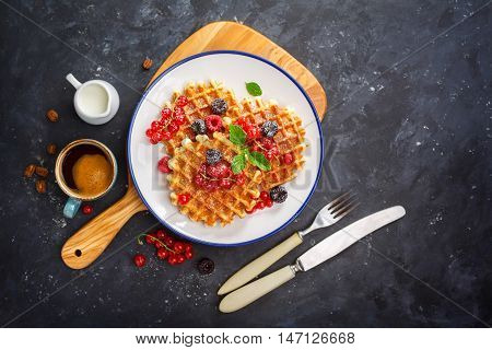 Waffles with fresh berries and honey. Breakfast with Belgian waffles, top view