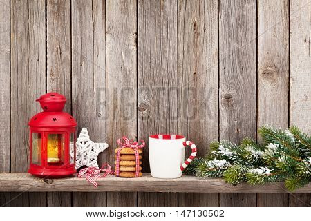 Christmas candle lantern, food and decor in front of wooden wall with copy space