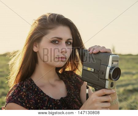 girl with a cinema camera on a meadow at sunset