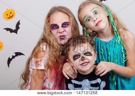 Happy brother and two sisters on Halloween party. People having fun indoor. Children wearing costumes zombies skeletons and witches. Concept of children ready for a party.