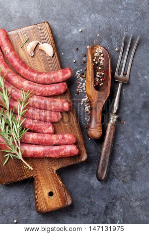 Raw sausages and ingredients for cooking. Top view on stone table