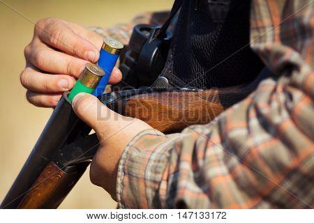 Close-up of a hunter loading his shotgun