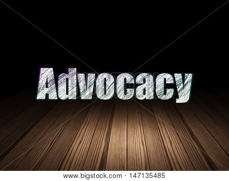 Law concept: Glowing text Advocacy in grunge dark room with Wooden Floor, black background