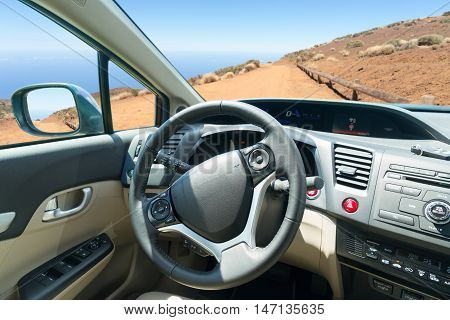 car windscreen with mountain ountry road, view inside out