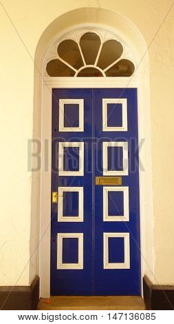 Blue door inset in wall and decorated with white rectangular motifs and with decorative glass above, Hull, England