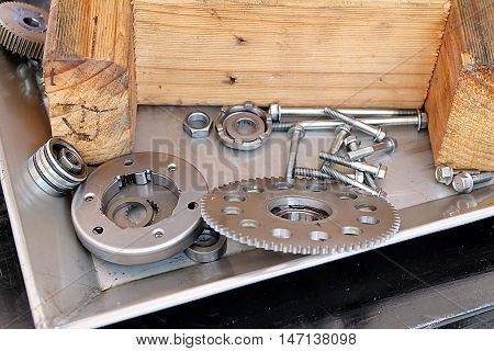 Steel gears, nuts, bolts, and wrenches. pieces of equipment in the system.