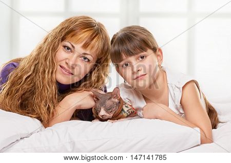 Portrait of a joyful mother and her daughter in the bed on light window bakground