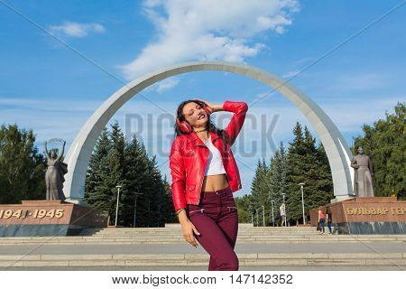 Girl in red jacket listening to music streaming with headphones and dancing on the street.
