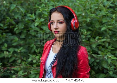 Girl in red jacket listening to music streaming with headphones on the gree background. Close up portrait.