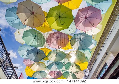 Colourful umbrellas hanging on the blue sky