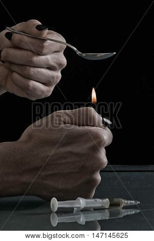 Cooking heroin in spoon, black background, close up