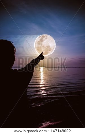 Silhouette back view of woman relax at seaside and pointing to the full moon on colorful sky background. Outdoors. Abstract full moon movement. The moon were NOT furnished by NASA.
