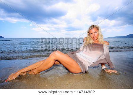 Young beautiful sexy blonde bikini model, laying on sea beach