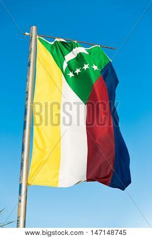 Waving National flag of Comoros on flagpole