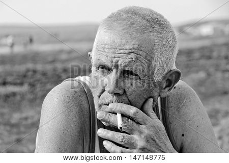 An elderly man smokes in nature. He is thoughtful and lonely.