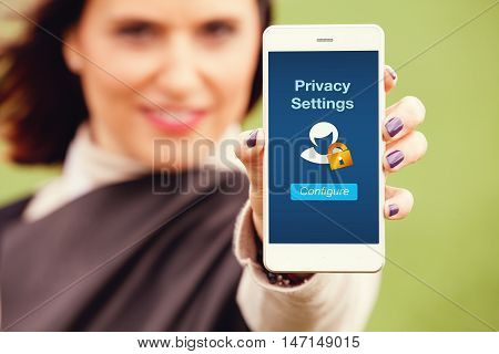 Privacy and security on mobile phone. Woman holding a smart phone with privacy settings menu in the screen.