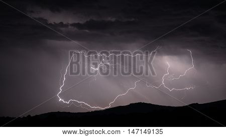 Closeup view of looping Lightning strike over mountain range