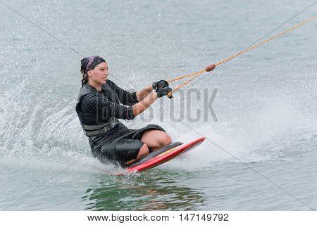 Young woman kneeboarding on lake, toned image, horizontal