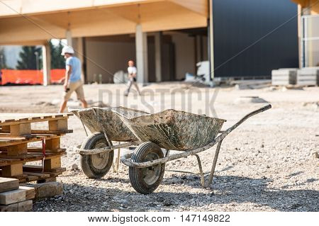 Two wheelbarrows in front of a construction site for small business premises. Property construction small scale enterprise expanding property concept.