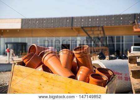 Wooden box filled with plastic pipes. Water drainage construction of a small business waste water piping construction concept.