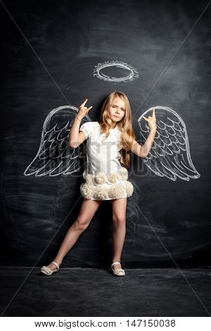 Pretty little angel girl. Cute child girl posing with angel wings drawn on a blackboard.