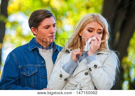 Betrayal and forgiveness couple. Girl is crying with handkerchief on outdoor. Man apologized and comforting his girlfriend.