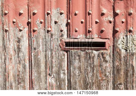 horizontal part of old wooden door with letter box and bladdered red paint in sunshine