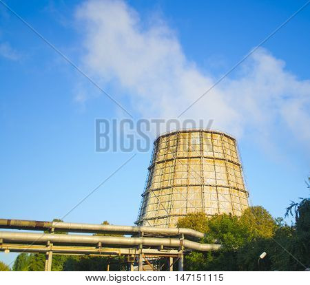 large pipe plant with smoke on a sunny day with clear blue sky in summer
