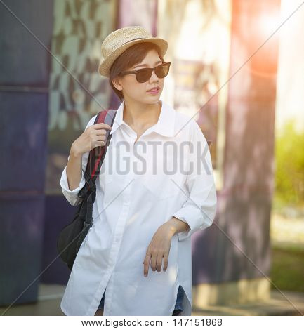 portrait of younger asian woman wearing straw hat and sun glasses relaxing traveling