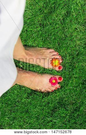 Top-down perspective of female feet decorated with flowers on green grass